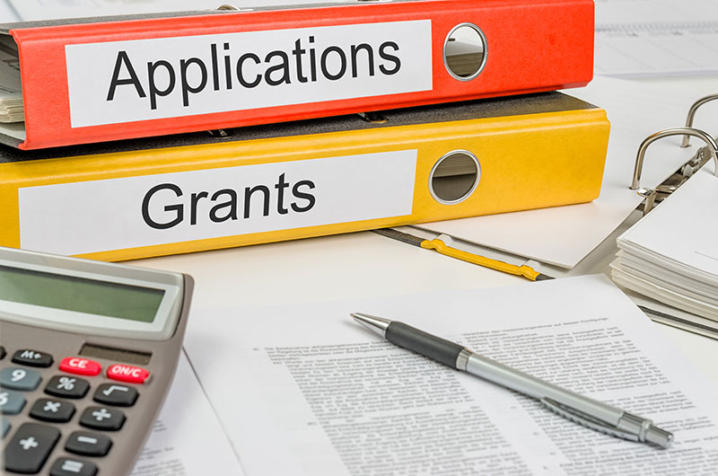 A desktop full of binders and grant proposals. Two binders are prominent, labeled Applications and Grants.